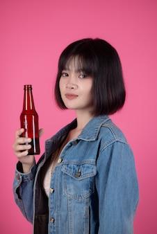Mujer joven con botella de cerveza cerveza en rosa