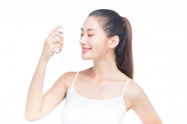 Mujer joven con botella de loción y spray para enfrentar