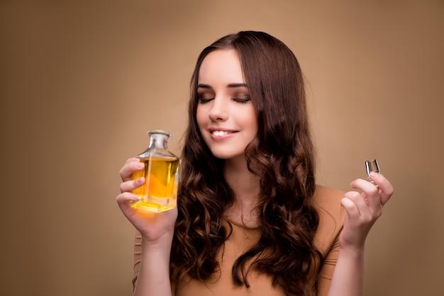 Mujer joven con botella de perfume