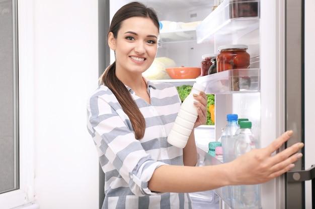 Mujer joven con una botella de yogur cerca de la nevera abierta en casa