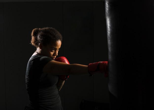 Mujer joven boxeando en el gimnasio