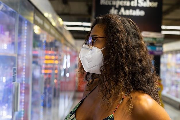Mujer joven brasileña de compras en el supermercado con máscara. nuevo concepto de normalidad.