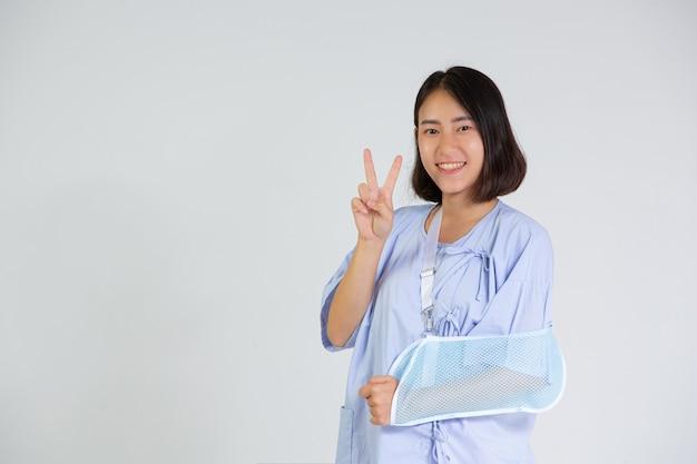 Mujer joven con un brazo roto con una férula de brazo