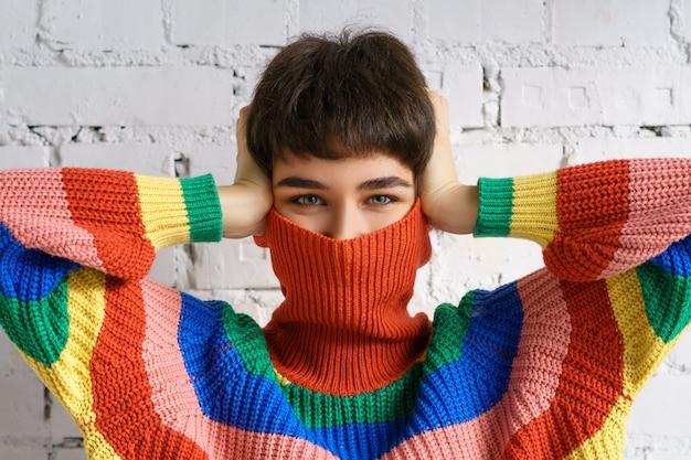 Una mujer joven con un brillante suéter multicolor del arco iris esconde su rostro y cubre sus orejas con sus manos.