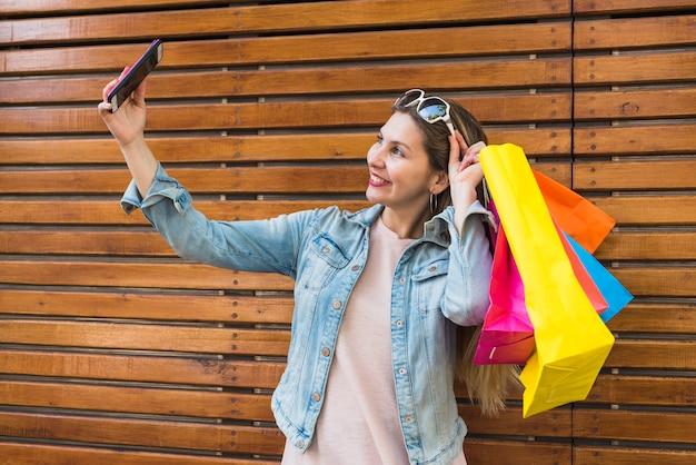 Mujer joven con brillantes bolsas de compras tomando selfie