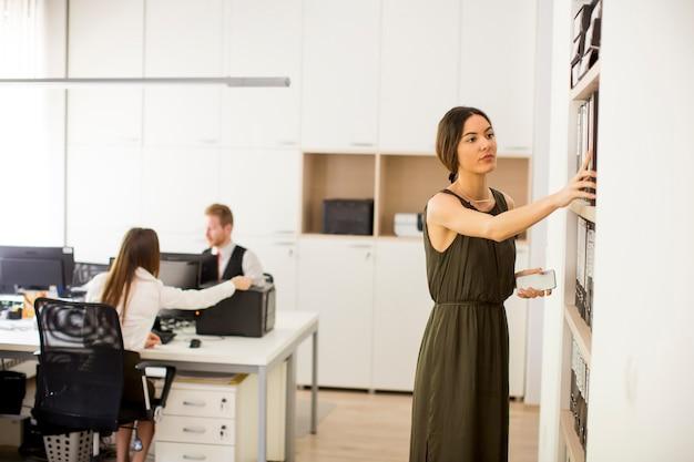 Mujer joven buscando algo en la oficina