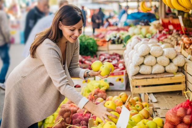 La mujer joven está buscando manzanas en el mercado verde.