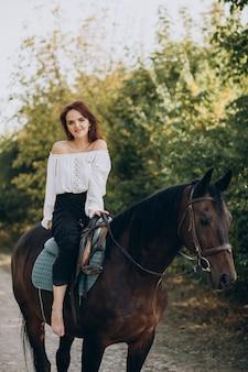 Mujer joven a caballo en el bosque