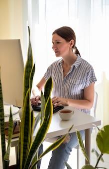 Mujer joven con cabello castaño trabaja en una computadora de escritorio en casa en cuarentena