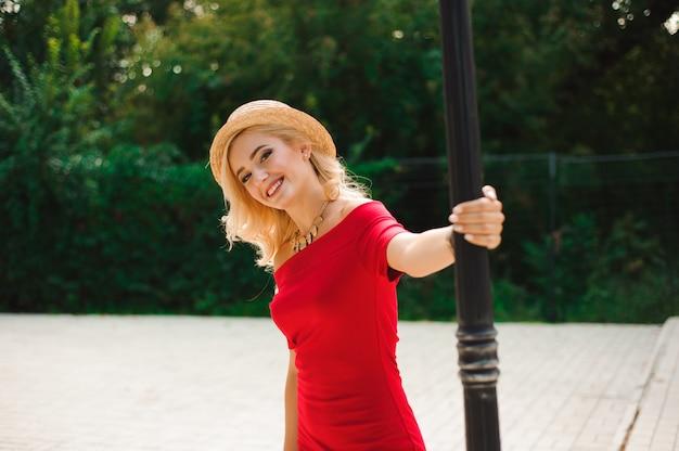 Mujer joven con cabello largo y brillante alegremente posando mientras camina afuera de buen humor