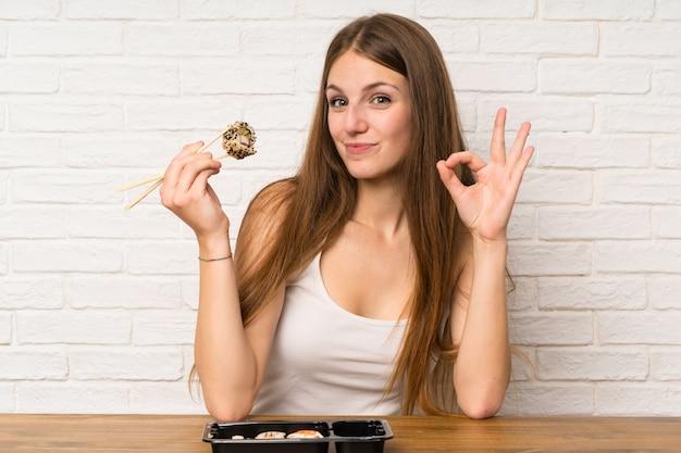 Mujer joven con cabello largo comiendo sushi y haciendo señal de ok