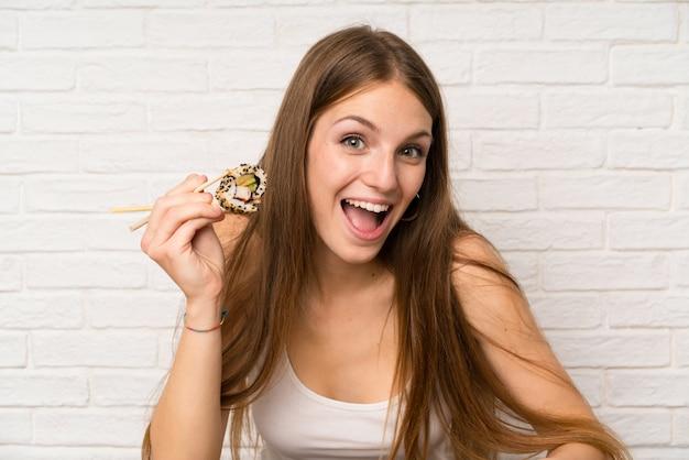 Mujer joven con cabello largo comiendo sushi