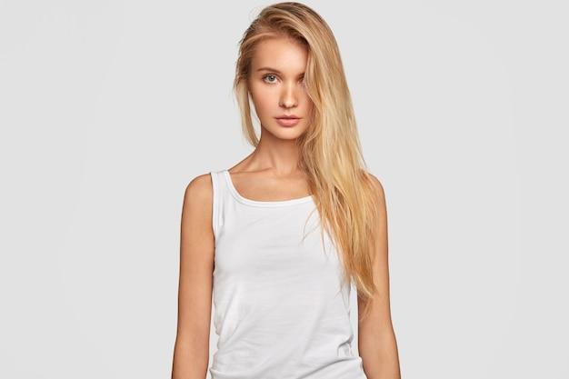 Mujer joven con cabello largo rubio peinado en un lado, viste camiseta blanca casual de gran tamaño