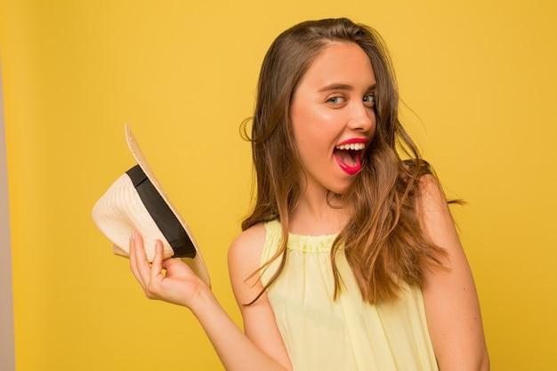 Mujer joven con cabello ondulado expresando emociones positivas sobre pared amarilla