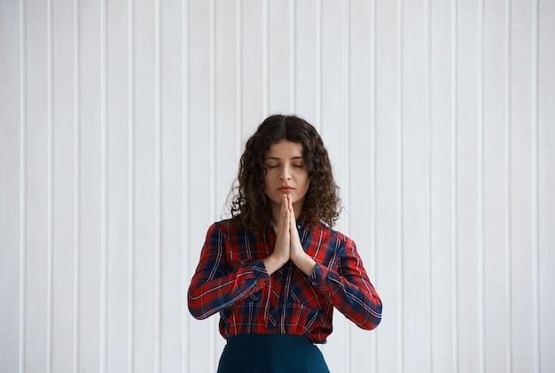 Mujer joven con cabello rizado y camisa a cuadros rezando
