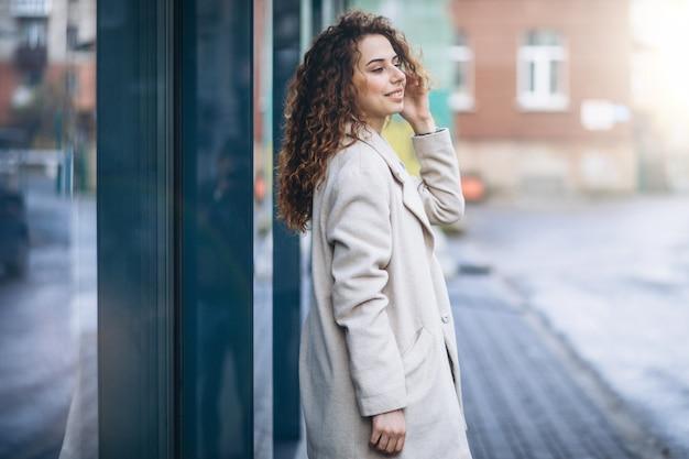 Mujer joven con cabello rizado fuera de la calle