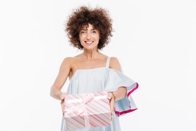 Mujer joven con cabello rizado mostrando caja de regalo
