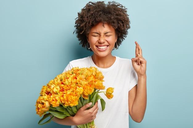 Mujer joven con cabello rizado con ramo de flores amarillas