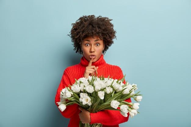 Mujer joven con cabello rizado con ramo de flores blancas
