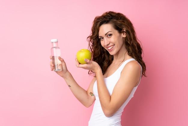 Mujer joven con cabello rizado sosteniendo una manzana y una botella de agua sobre rosa aislado