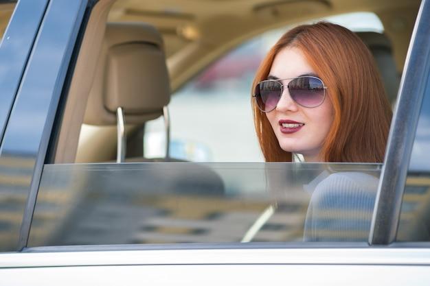 Mujer joven con cabello rojo y gafas de sol viajando en coche