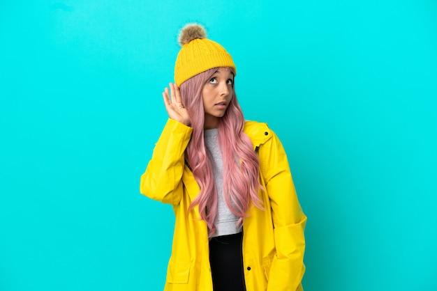 Mujer joven con cabello rosado con un abrigo impermeable aislado sobre fondo azul escuchando algo poniendo la mano en la oreja