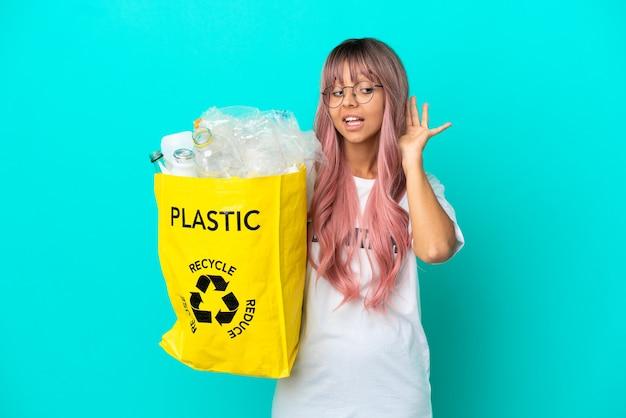 Mujer joven con cabello rosado sosteniendo una bolsa llena de botellas de plástico para reciclar aislado sobre fondo azul escuchando algo poniendo la mano en la oreja