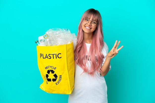 Mujer joven con cabello rosado sosteniendo una bolsa llena de botellas de plástico para reciclar aislado sobre fondo azul feliz y contando tres con los dedos