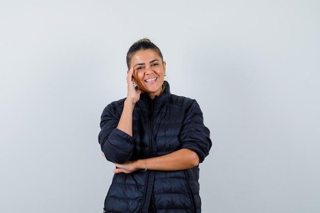 Mujer joven con la cabeza inclinada en la mano en chaqueta acolchada y aspecto alegre. vista frontal. Foto gratis