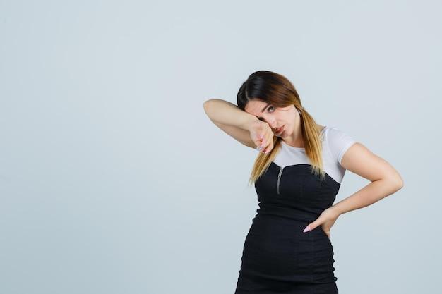 Mujer joven con la cabeza inclinada sobre el codo y mirando agotado