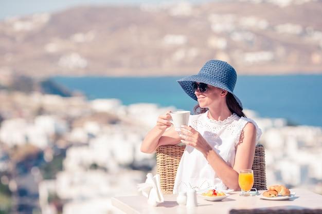Mujer joven con café en el café al aire libre con impresionantes vistas de la ciudad de mykonos.