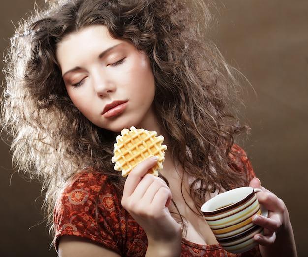 Mujer joven con café y galletas