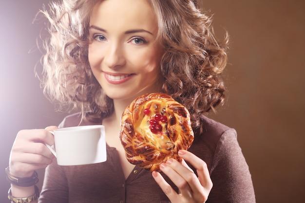 Mujer joven con café y pastel