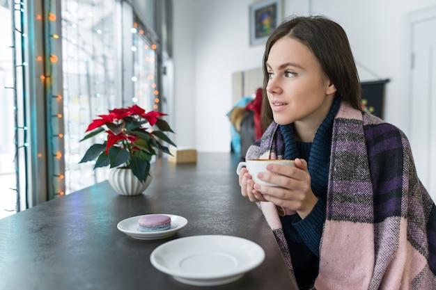 Mujer joven en café con una taza de bebida caliente con una manta caliente