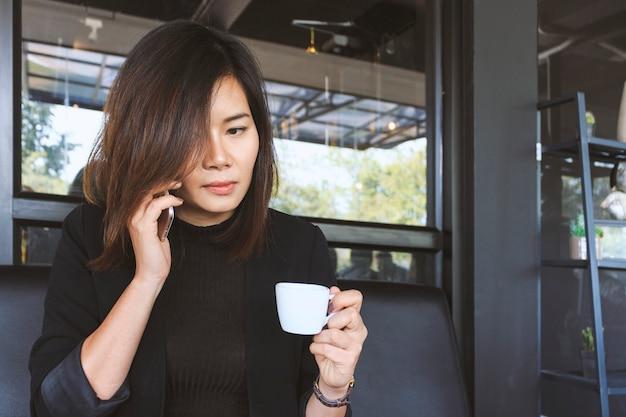 Mujer joven en el café tomando café y hablando por teléfono móvil