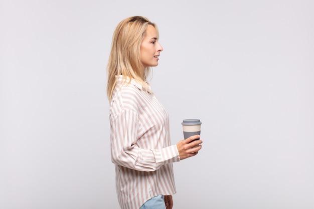 Mujer joven con un café en la vista de perfil mirando para copiar el espacio por delante, pensando, imaginando o soñando despierto
