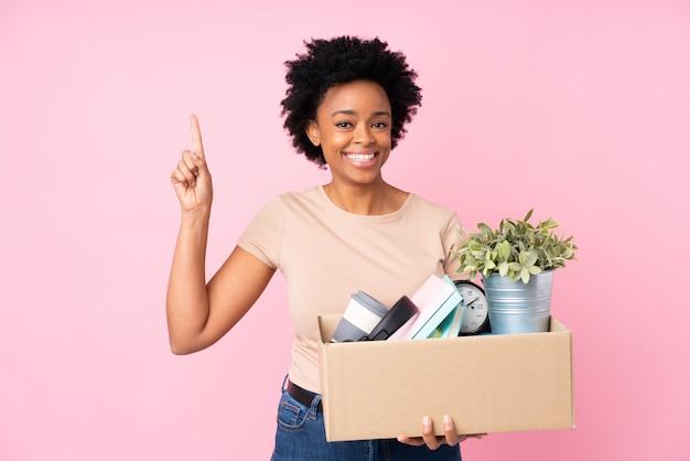 Mujer joven con caja llena de cosas sobre pared aislada