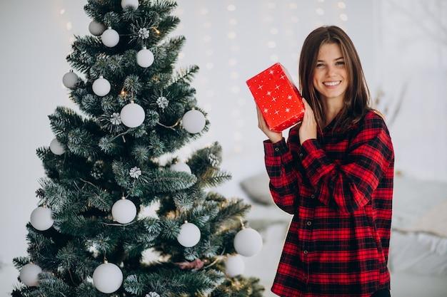 Mujer joven con caja de regalo por el árbol de navidad