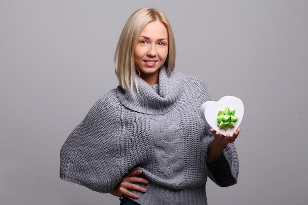 Mujer joven con caja de regalo en forma de corazón para san valentín