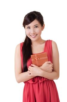 Mujer joven con caja de regalo, retrato de portarretrato sobre fondo azul de estudio.