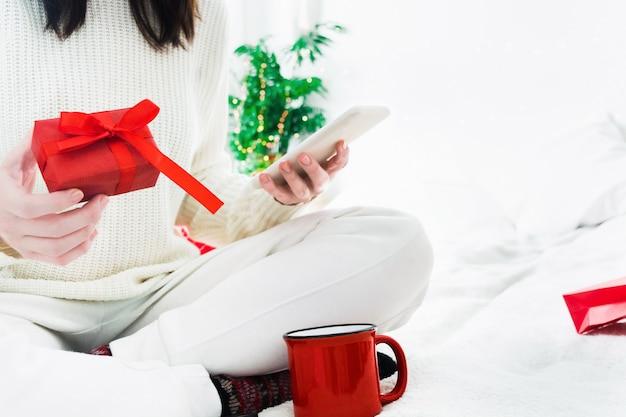 Mujer joven con caja de regalo roja y teléfono en manos y taza roja de bebida