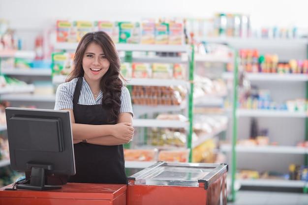 Mujer joven en caja registradora en una tienda