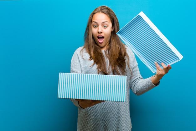 Mujer joven con una caja sobre fondo azul