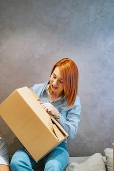 Mujer joven con cajas de cartón y lo sacude