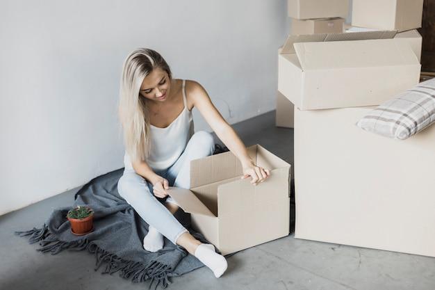 Mujer joven con cajas en el piso