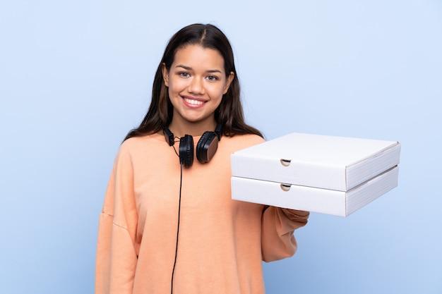 Mujer joven con cajas de pizza sobre pared aislada
