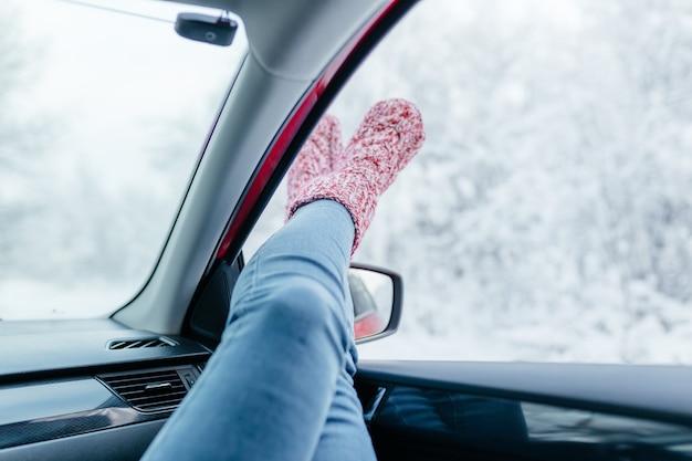 Mujer joven en calcetines calientes descansando dentro del coche, primer plano.