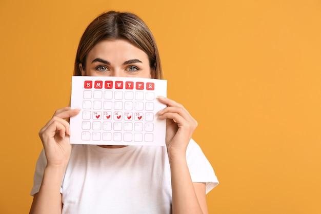 Mujer joven con calendario menstrual en superficie de color