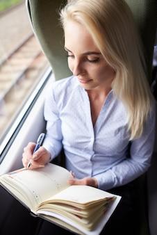 Mujer joven con calendario viajando en tren