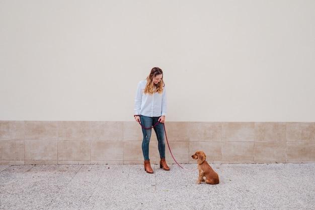 Mujer joven en la calle caminando con su lindo perro cocker. estilo de vida al aire libre con mascotas